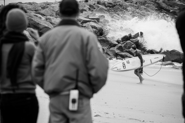 A life guard looks on as a surfer exits the water.